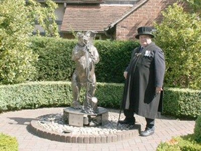 A Bailif in uniform, stood next to a statue of the Warwickshire Bear & ragged staff