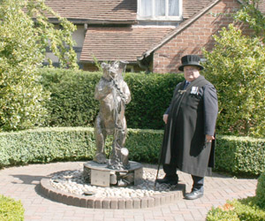 A Bailifs standing in front of a sculpture ofthe Warwickshire Bear and Ragged Staff symbol